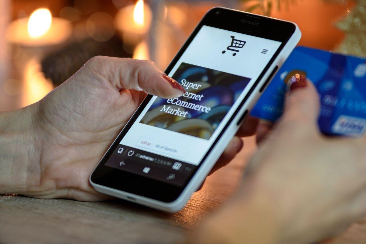Mano de mujer en un móvil con tarjeta de crédito dispuesta a comprar online